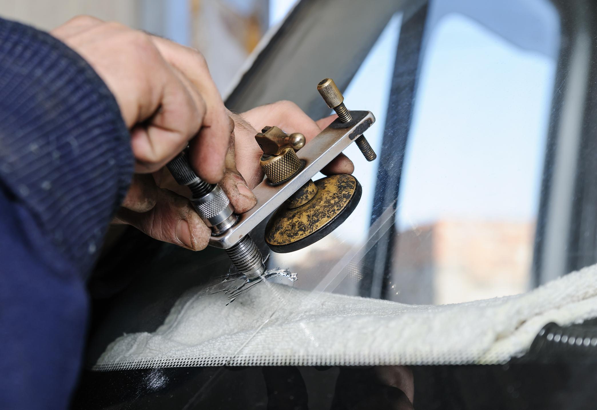 Repair cracked windshield. Fitter is using Windshield Repair Crack Bridge.