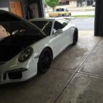 White Porsche with the hood open